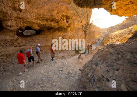 Africa, Namibia. Sossus Dune Lodge.  Namib Desert. Sossusvlei, Naukluft Park. People hiking in canyon. - Stock Photo