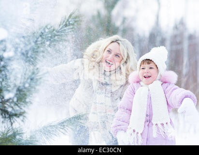 Happy mopther and kid playing with snow in winter outdoor - Stock Photo