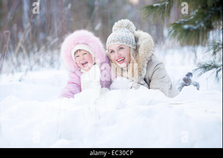 Happy mother and kid lying in snow outdoor - Stock Photo