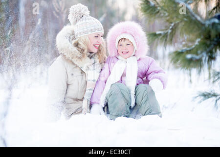 Happy family sitting in snow outdoor wintertime - Stock Photo
