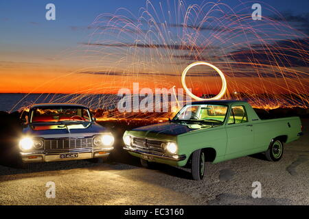 A light-painting of a 1967 Holden HR ute and 1964 Chevrolet Impala, with steel wool spinning in background. - Stock Photo