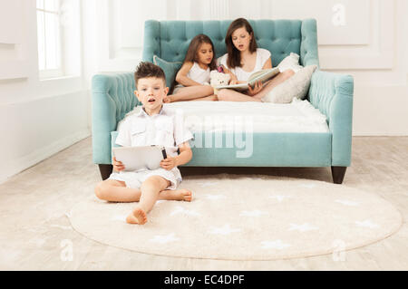 Siblings spending free time at home: two girls reading book on couch and boy using tablet while sitting on floor - Stock Photo