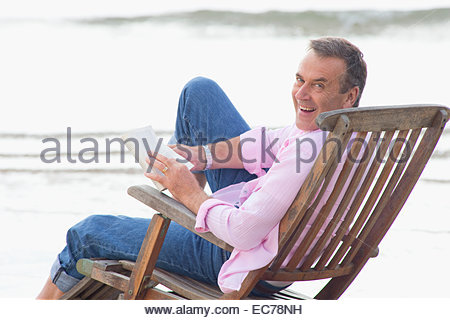 Older man reading book in deck chair on beach - Stock Photo