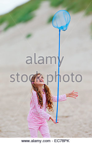 Girl balancing butterfly net on finger on beach - Stock Photo
