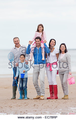 Multi-generation family smiling together on beach - Stock Photo