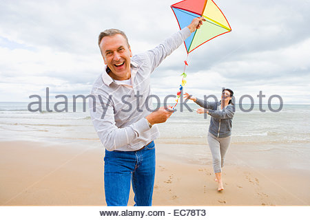 Older couple flying kite on beach - Stock Photo