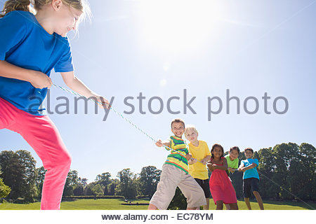 Group of children playing tug of war in park - Stock Photo