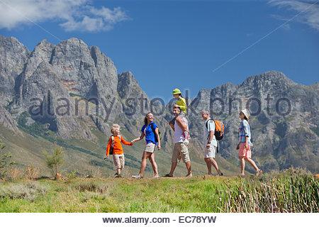 Multi generation family hiking on mountain path - Stock Photo