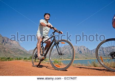 Senior man mountain biking on country track - Stock Photo