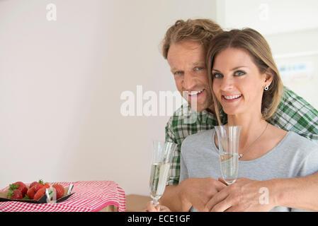 New apartment couple celebrating drinking - Stock Photo