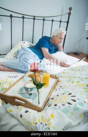 Mature man having breakfast in bed with digital tablet, smiling - Stock Photo