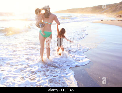 Mother walking away in surf along sandy beach, carrying her son (2-3) and leading daughter by hand - Stock Photo