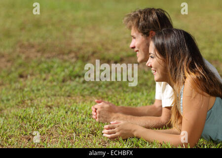 Profile of a couple lying on the grass and looking away with a green background - Stock Photo