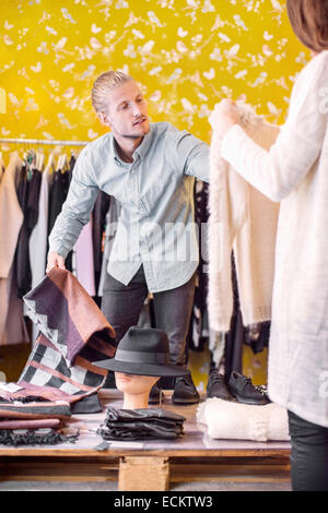 Male owner helping female customer in boutique - Stock Photo
