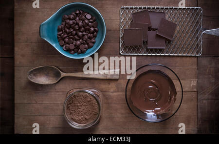 Top down view of chocolate baking supplies laid out on a rustic wood surface with antique props. - Stock Photo