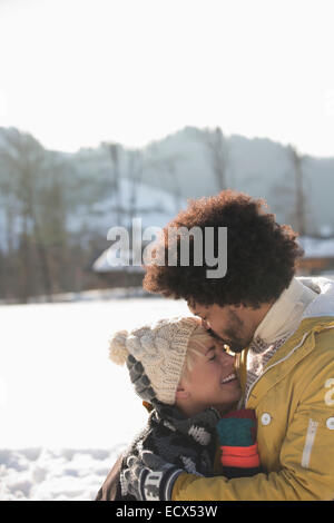 Man kissing woman's forehead in snow - Stock Photo