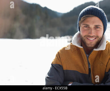 Portrait of smiling man in snow - Stock Photo