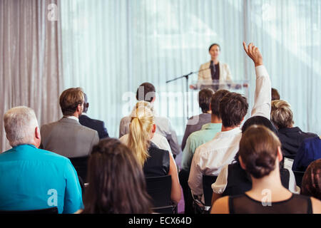 Businesswoman giving presentation in conference room, people raising hands - Stock Photo