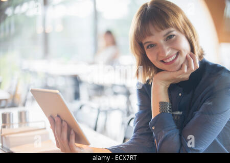 Businesswoman using digital tablet in cafeteria - Stock Photo