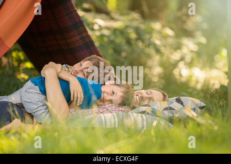 Father and sons relaxing together near camping tent - Stockfoto