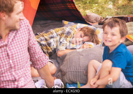 Father and sons smiling at camping tent - Stock Photo