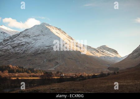Afternoon sun on the snowy volcanic peaks of Glen Coe, Scotland, in the Scottish Highlands. A farmhouse is lit by - Stock Photo