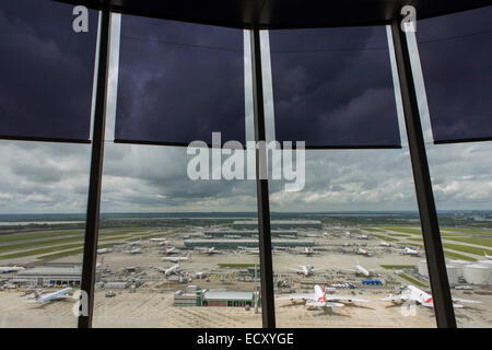 Aerial view (through control tower windows) showing expanse of airport land with airliners at London Heathrow. - Stock Photo