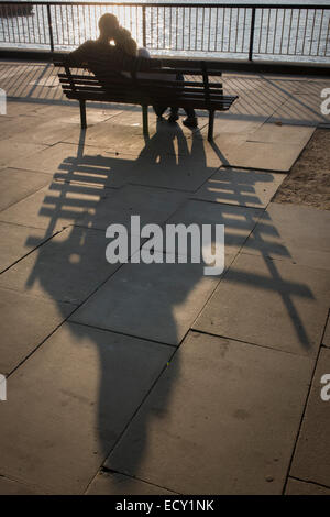Couple share intimate moment in late afternoon on London's Southbank. - Stock Photo