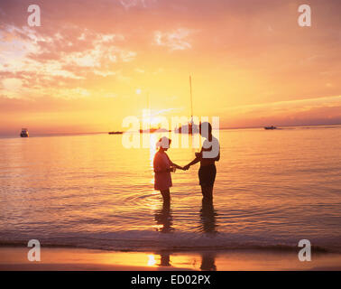 Couple in sea at sunset, Negril Beach, Negril, Westmoreland Parish, Jamaica, Greater Antilles, Caribbean - Stock Photo