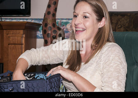 20's female sitting in a chair.  She is smiling and has braces.  There is a blue zipper bag on her lap - Stock Photo