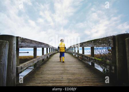 Boy (4-5) walking across wooden bridge - Stock Photo