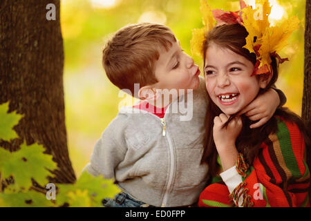 Boy hugging a girl, trying to kiss her - Stock Photo