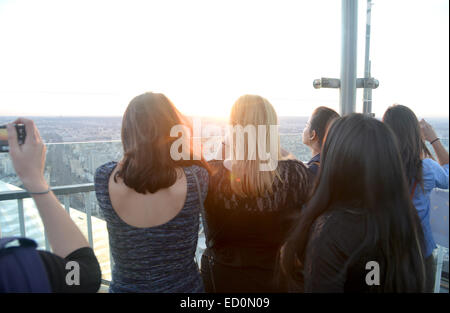 Group of girls watch and photograph the Paris sunset from the top of the Montparnasse Towet - Stock Photo