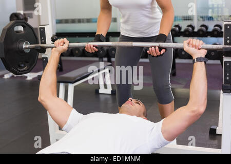 Trainer helping man with lifting barbell in gym - Stock Photo