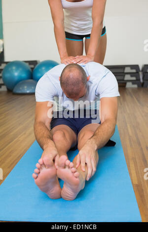 Trainer assisting man with stretching exercises at fitness studio - Stockfoto