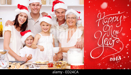 Composite image of children baking christmas cakes in the kitchen with their family - Stock Photo