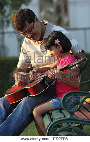 Indian man assisting his granddaughter in playing guitar - Stockfoto