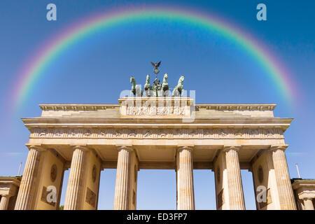 brandenburger tor and rainbow on blue sky in berlin - Stock Photo