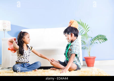 2 indian children home playing Teddy Bear - Stock Photo