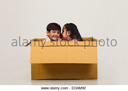 Indian sister whispering to her brother ear - Stockfoto