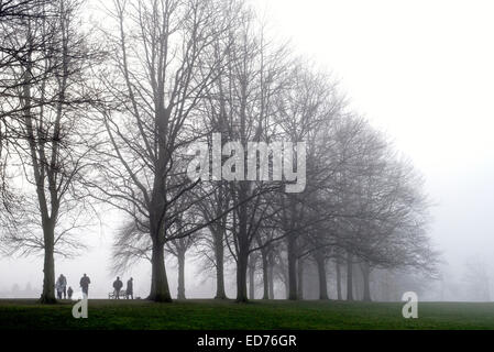 Walkers on a misty winter's day taking a stroll in Inverleith Park, Edinburgh, Scotland, UK. - Stock Photo