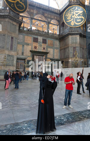 Muslim woman at Hagia Sophia, Ayasofya Muzesi mosque museum wearing niqab using smartphone taking photographs, Istanbul, - Stock Photo