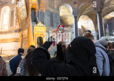 Muslim woman at Hagia Sophia, Ayasofya Muzesi mosque museum wearing niqab using smartphone to take photographs, - Stock Photo
