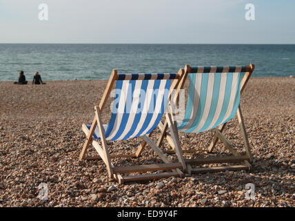 Two empty deck chairs on Brighton beach with two people and sea in the distance on sunny day - Stockfoto