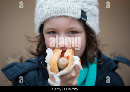 London, UK. 01st Jan, 2015. A girl enjoys a hot dog. Winter Wonderland in Hyde Park contuinues to draw large crowds - Stock Photo