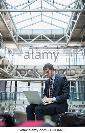 Businessman using laptop at airport - Stock Photo
