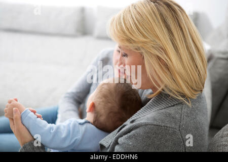 Mother sitting with daughter and baby boy on couch - Stock Photo