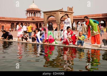 Devout Muslims purifying themselves in the water basin of the Friday Mosque Jama Masjid, Delhi, India - Stock Photo