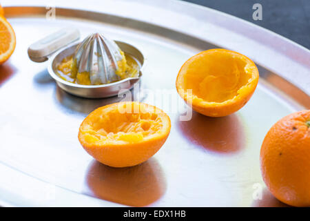 freshly squeezed oranges on a silver tray with silver metal hand juicer. - Stock Photo