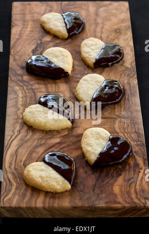 homemade chocolate dipped heart biscuits or cookies on olive wood board - Stock Photo